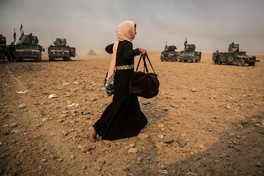 A woman tries to get away from the fighting as Iraqi forces enter Topzawa, on the outskirts of Mosul.
